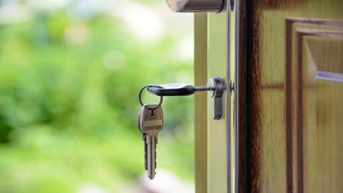 the house key hanging in the door lock.