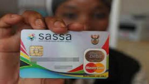 SASSA beneficiary holding up SASSA card