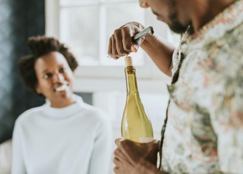 man uncorking a wine bottle