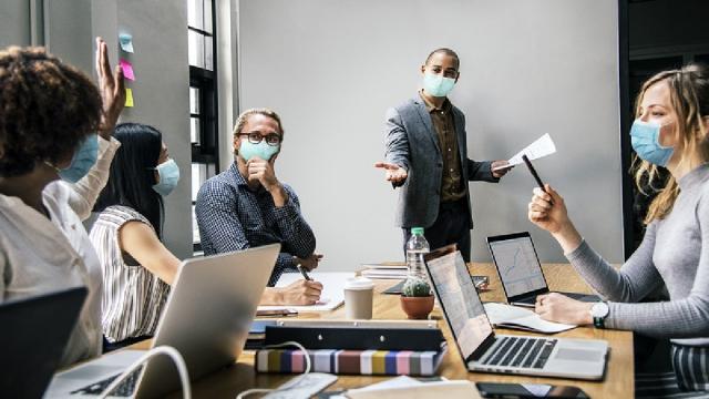 employees in an office wearing masks